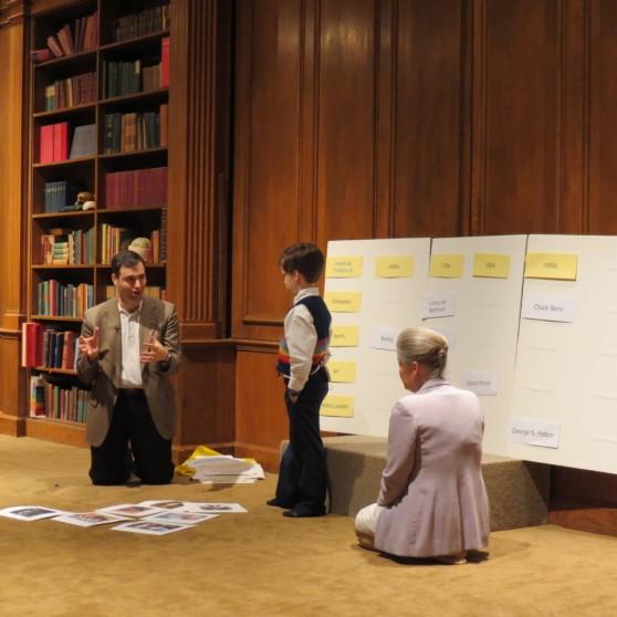 Jake y su papá construyen, junto a Janet Doman, una línea del tiempo en la demostración del curso Cómo Multiplicar la inteligencia de su bebé.